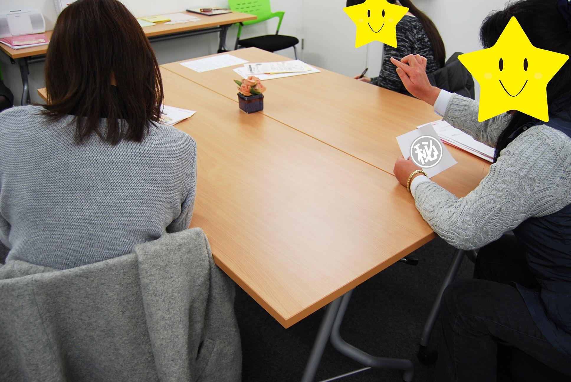 一人が紙に書かれた内容を言葉で伝えて、二人が聞き取った内容を紙に再現しています。